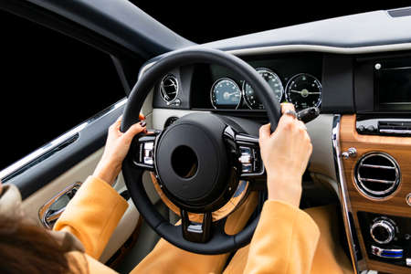Womans hands on the steering wheel driving modern luxury car. Concept woman driving. Hands holding steering wheel while driving. Car inside. Car detailing.