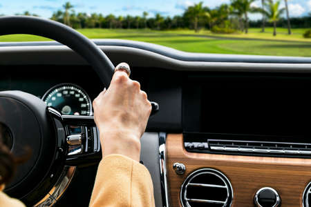 Woman's hands on the steering wheel driving modern luxury car. Concept woman driving. Hands holding steering wheel while driving. Car inside. Car detailing.