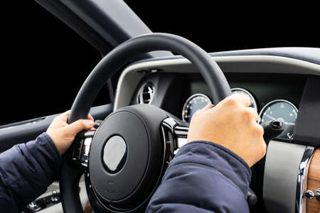 Male hands holding car steering wheel. Hands on steering wheel of a car driving. Young Man driving a car inside cabin. Multimedia system. Man Traveling In Self Driving Car. Car inside. Driving concept