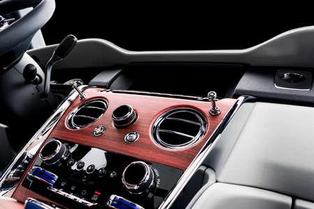 Interni in pelle bianca per auto di lusso moderna con pannello in legno naturale. Parte dei dettagli del seggiolino auto in pelle con cuciture. Interni di prestigiose auto moderne. Pelle traforata bianca. Dettagli auto. Auto dentro