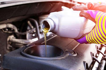 Verander de olie. Handmonteur bij het repareren van auto. Close-up olie voor motor van een auto. Motorolie die naar de motor van een auto stroomt. Tanken en olie in de motormotor gieten. Onderhoud. Auto detaillering Stockfoto
