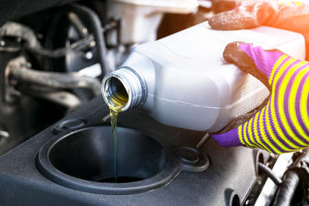 Change the Oil. Hand mechanic in repairing car. Close up oil for car engine. Motor oil pouring to car engine. Refueling and pouring oil into the engine motor. Maintenance. Car detailing