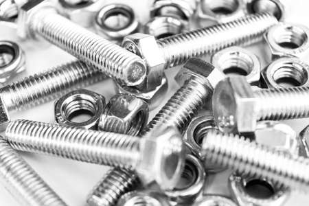 Metal bolts and nuts in a row background. Chromed screw bolts and nuts isolated. Steel bolts and nuts pattern. Set of Nuts and bolts. Tools for work. Black and white Archivio Fotografico