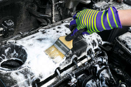 A man cleaning car engine with shampoo and brush. Car detailing or valeting concept. Selective focus. Car detailing. Cleaning with sponge. Worker cleaning. Car wash concept solution to clean Stock Photo