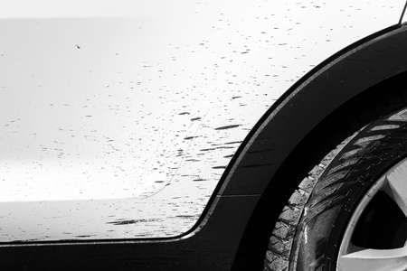 Side view of a very dirty car with bitumen stain. Fragment of a dirty SUV. Dirty headlights, wheel and bumper of the off-road car with swamp splashes on a side panel