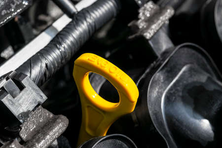 Yellow oil dipstick in car engine. Measuring level of engine oil. Dipstick oil level gauge with yellow color for Checking engine oil level of engine system.