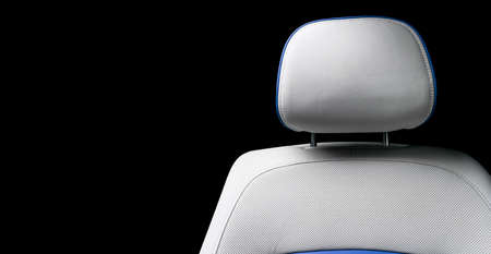 White leather interior of the luxury modern car. Perforated white leather comfortable seats with stitching isolated on black background. Modern car interior details. Car detailing. Car inside.