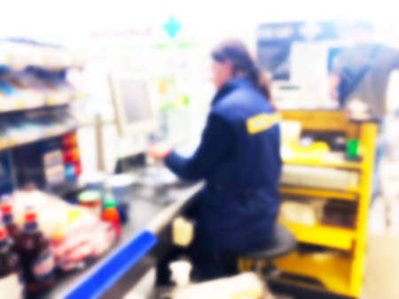 Blurred background of cashier with long line of people at check-out counter of supermarket. Blur Customers paying cash to store clerks, full cart of groceries. Cashier register concept. Blurred store