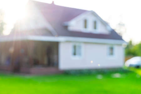 Blurred abstract background of Luxury house. House exterior theme creative abstract blur background with bokeh effect. Blurred house and lawn Imagens