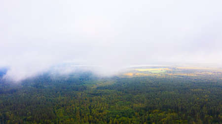 Aerial Drone view clouds over the green forest and lake. Low lying cloud. Aerial view of over tropical rainforest. Above the clouds in the sky. Top view from drone Imagens