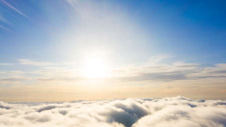 Aerial view White clouds in blue sky. Top view. View from drone. Aerial birds eye view. Aerial top view cloudscape. Texture of clouds. View from above. Sunrise or sunset over clouds