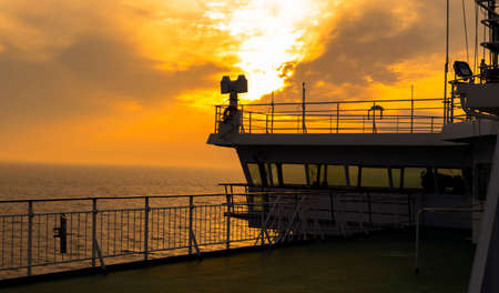 Cruise ship white cabin with big windows. Wing of running bridge of cruise liner. White cruise ship on a blue sky with radar and navigation system. Captains cabin. Ocean sunset background Imagens
