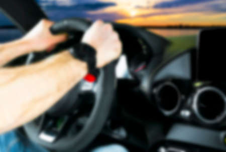 Blurred image of car interior with man driving. Dashboard. Blur, defocused transportation background. Driving inside car. Bokeh light background