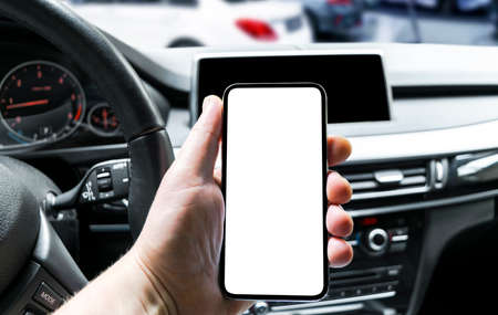 Male hand using smartphone in car. Man driving a car. Smartphone in a car use for Navigate or GPS. Mobile phone with isolatede white screen. Blank empty screen. copy space. Empty space for text. Imagens