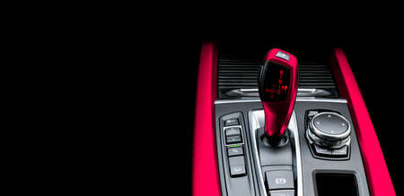 Red Automatic gear stick of a modern car. Maodern car interior details. Close up view. Car detailing. Automatic transmission lever shift isolated on black background. Black leather interior with stitching. Imagens