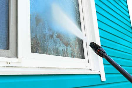 Reinigungsservice, der Gebäudefassade und Fenster mit Druckwasser wäscht. Schmutzige Wand mit Hochdruckwasserstrahl reinigen. Macht die Wand wäscht. Reinigung der Fassade des Hauses. Vor und nach dem Waschen