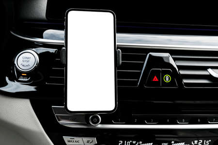 Smartphone in a car use for Navigate or GPS. Driving a car with Smartphone in holder. Mobile phone with isolatede white screen. Blank empty screen. copy space. Empty space for text. Imagens - 133624248