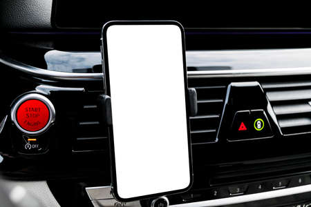 Smartphone in a car use for Navigate or GPS. Driving a car with Smartphone in holder. Mobile phone with isolatede white screen. Blank empty screen. copy space. Empty space for text. Imagens