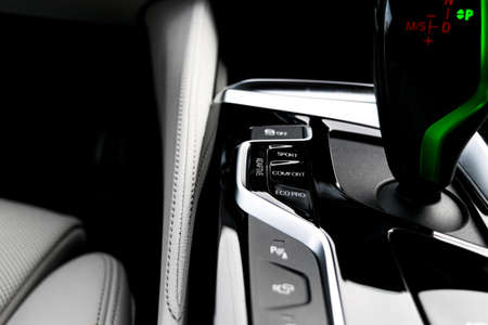 Modern luxury car white leather interior with natural wood panel. Part of leather car seat details with stitching. Interior with dashboard. White perforated leather. Car detailing. Car inside