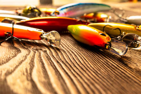 Fishing tackle background. Fishing tackles and wobbler on wooden board. Fishing hooks, lures and baits. Fishing gear on a dark table