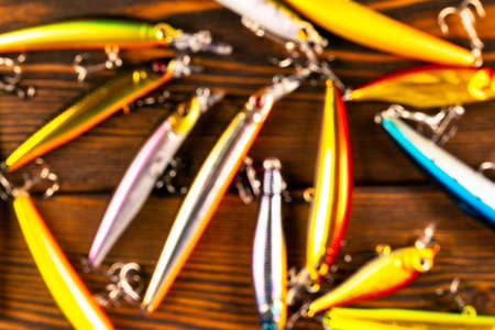 Blurred background with fishing tackle. Defocused fishing tackles and wobbler on wooden board. Fishing hooks, lures and baits. Blurry fishing gear on a dark table