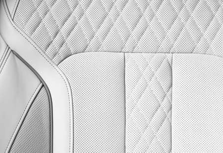 Modern luxury Car white leather interior. Part of perforated leather car seat details. White Perforated leather texture background. Texture, artificial leather with stitching. Perforated leather seats