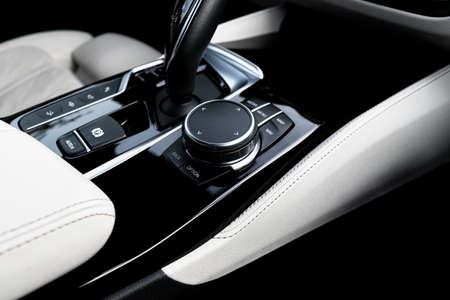Media and navigation control buttons of a Modern car. Car interior details. White leather interior with stitching. Car detailing Imagens