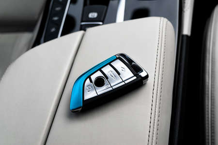 Closeup inside vehicle of wireless key ignition on white perforated leather seat. Wireless start engine key. Car key remote isolated. Modern Car keys detailing. Car keys close up.