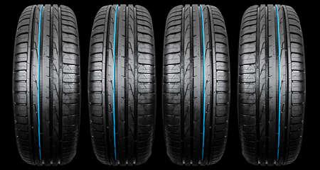 Foto de estudio de un conjunto de neumáticos de coche de verano aislado sobre fondo negro. Pila de neumáticos. Protector de neumáticos de coche de cerca. Neumático de caucho negro. Neumáticos de coche nuevos. Cierre el perfil del neumático negro. Neumáticos de coche en una fila