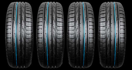Studio shot di una serie di pneumatici per auto estivi isolati su sfondo nero. Pila di pneumatici. Primo piano di protezione per pneumatici per auto. Pneumatico in gomma nera. Pneumatici per auto nuovi di zecca. Chiuda sul profilo del pneumatico nero. Pneumatici per auto di fila