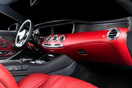 Interni auto moderne di lusso rosso con volante, leva del cambio e cruscotto. Tracciato di ritaglio. Dettaglio degli interni delle auto moderne. Leva del cambio automatico. Parte di sedili in pelle con cuciture in auto costose