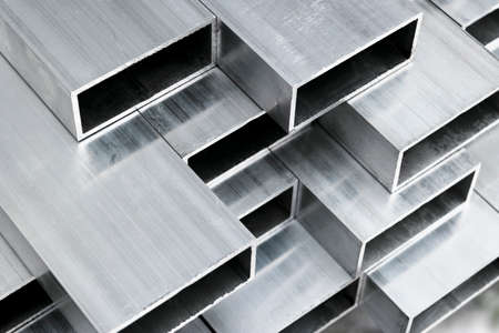 Aluminium profile for windows and doors manufacturing. Structural metal aluminium shapes. Aluminium profiles texture for constructions. Aluminum constructions factory background.