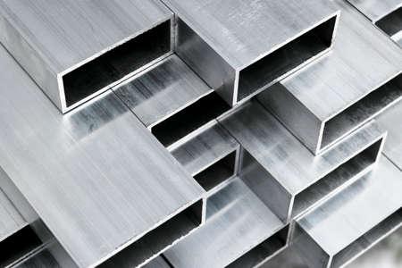 Profilo in alluminio per la produzione di finestre e porte. Forme strutturali in alluminio metallico. Texture di profili in alluminio per costruzioni. Fondo di fabbrica di costruzioni in alluminio.