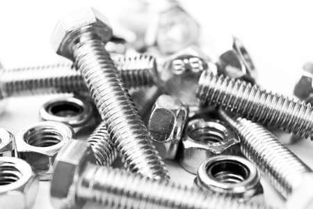 Metal bolts and nuts  in a row background. Chromed screw bolts and nuts isolated. Steel bolts and nuts pattern. Set of Nuts and bolts. Tools for work. Black and white 免版税图像