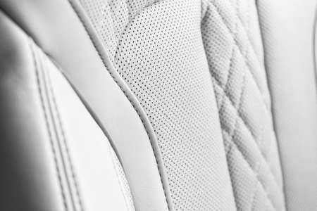 Modern luxury Car white leather interior. Part of perforated leather car seat details. White Perforated leather texture background. Texture, artificial leather with stitching. Perforated leather seats Archivio Fotografico