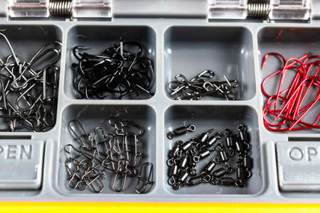 Opened tackle box with fishing hooks and accessories. Fishing hooks in box sections. Case for tackle elements. Fishing accessories background close-up.