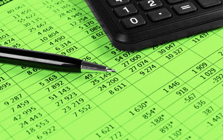Financial concept. Calculator, pen and glasses on financial documents. Financial accounting. Balance sheets. Closeup of financial statements and annual reports. Business marketing