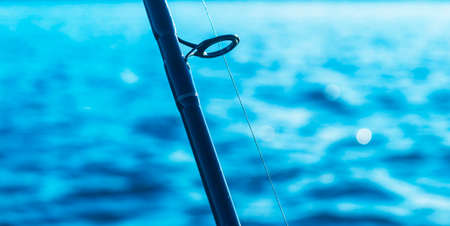 Fishing rod spinning rod with the line close-up. Fishing rod. Fishing tackle. Fishing spinning reel over blue ocean water