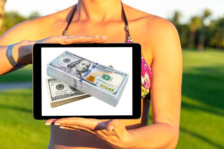 Make money online. Business concept with making profit using internet. Laptop computer with money in woman hands. Making money online concept. Using a laptop to building online business 写真素材