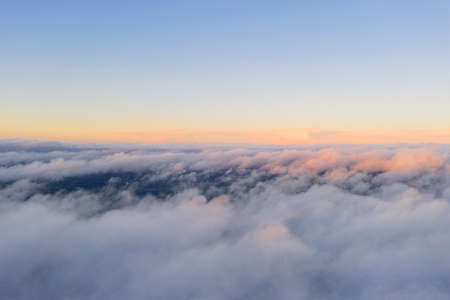 Aerial view White clouds in blue sky. View from drone. Aerial top view cloudscape. Texture of clouds. View from above. Sunrise or sunset over clouds. Panorama clouds 写真素材