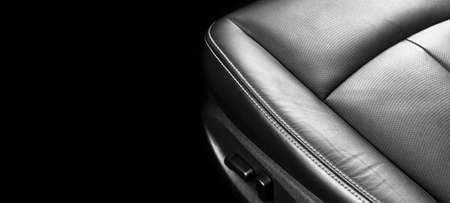 Luxury car black leather interior. Part of leather car seat details with stitching. Interior of a modern car. Comfortable perforated leather seats. Perforated leather. Car detailing. Black and white