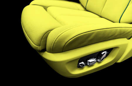 Yellow leather interior of the luxury modern car. Perforated yellow leather comfortable seats with stitching isolated on black background. Modern car interior details. Car detailing. Car inside