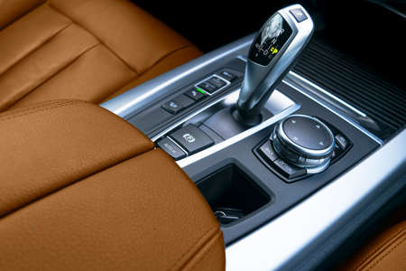 Automatic gear stick (transmission) of a modern car. Multimedia and navigation control buttons. Car interior details. Transmission shift. Brown leather interior. Foto de archivo