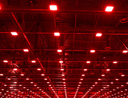 Red Lights and ventilation system in long line on ceiling of the dark office industrial building, exhibition Hall Ceiling construction