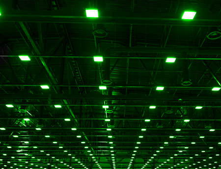 Green Lights and ventilation system in long line on ceiling of the dark office industrial building, exhibition Hall Ceiling construction Reklamní fotografie
