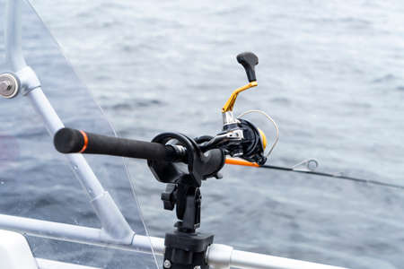 Fishing rod spinning with the line close-up. Fishing rod in rod holder in fishing boat. Fishing rod rings. Fishing tackle. Fishing spinning reel.