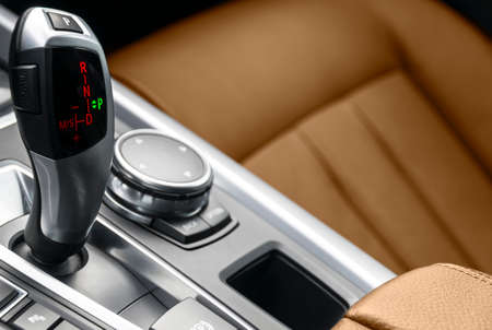 Automatic gear stick transmission of a modern car. Multimedia and navigation control buttons. Car interior details. Transmission shift. Brown leather interior.