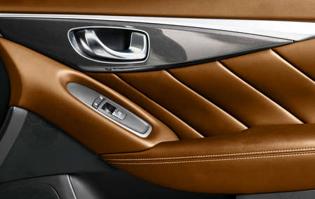 Door handle with power window control buttons of a luxury passenger car. Brown perforated leather interior with stitching. Modern car orange leather interior details.