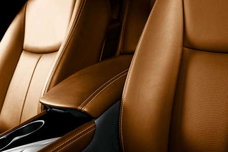 Brown leather interior of the luxury modern car. Perforated brown leather comfortable seats with stitching isolated on black background. Modern car interior details. Car detailing. Car inside