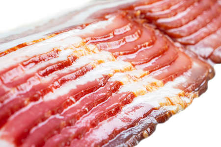 Several rows of sliced smoked bacon isolated on white background. Fresh sliced bacon isolated over white background. Raw dry-cured bacon.